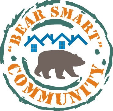 The Bear Smart Community Program logo, showing a bear walking in front of houses.