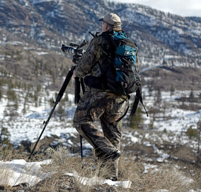 A wildlife photographer in full camouflage with his camera overlooking a valley.