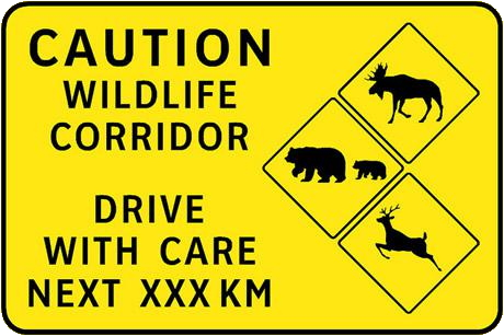 A roadsign sign says: Caution Wildlife Corridor